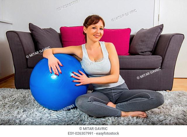 Fitness girl with pilates ball at home