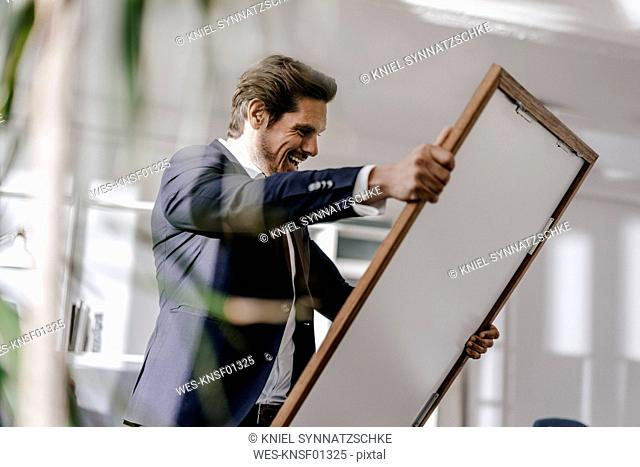 Excited businessman holding picture frame