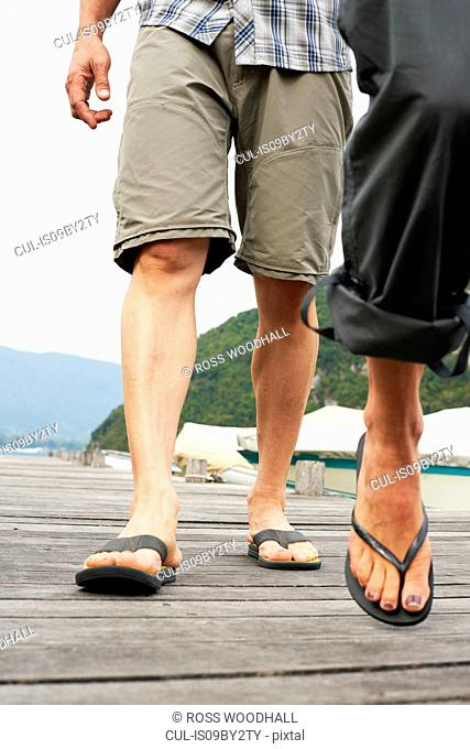 Mature couple strolling on Lake Annecy pier, cropped, Annecy, Rhone-Alpes, France