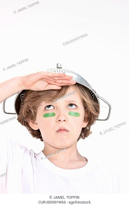 Boy pretending to be soldier wearing colander on head