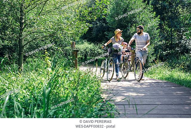 Family pushing bicycles on wooden walkway