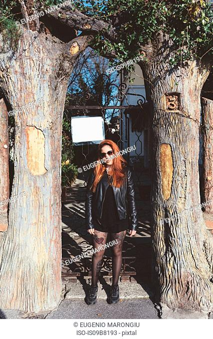 Portrait of red haired woman wearing sunglasses standing between trees