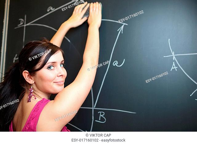Pretty, young college student drawing on the chalkboard/blackboard during a math class (shallow DOF color toned image)