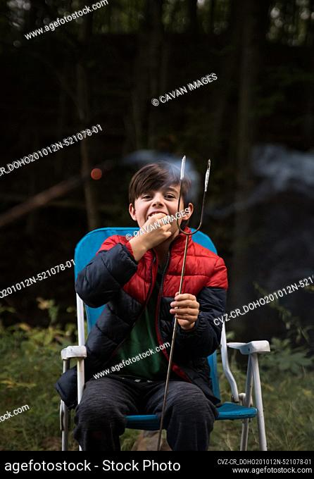 Young boy eating a marshmallow off of a metal stick outdoors