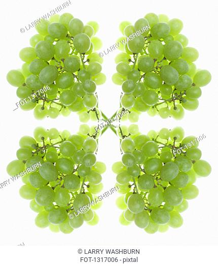 A digital composite of mirrored images of bunches of green grapes