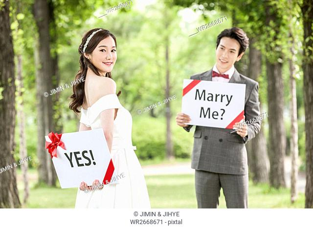 Young romantic wedding couple posing with English messages outdoors