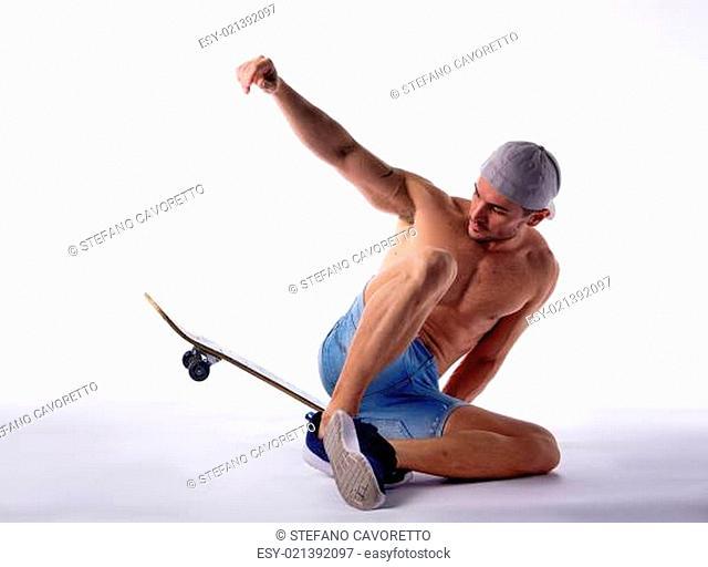 Shirtless Man Sitting on Skateboard in Studio