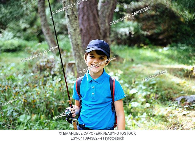 portrait of child with fishing rod in the mountains in the alps