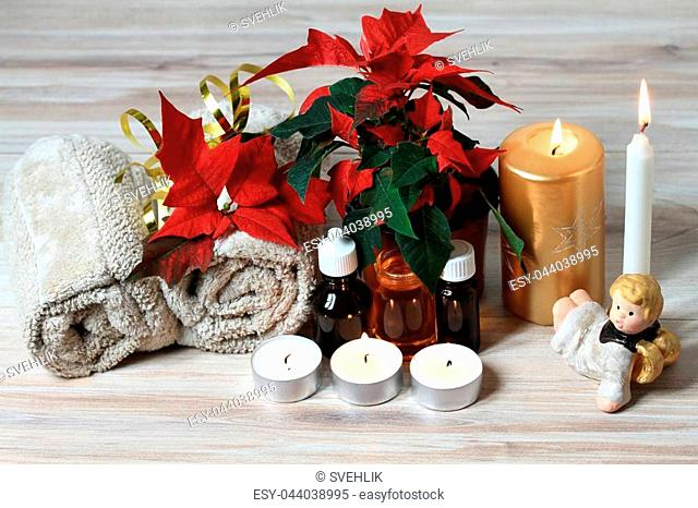 Wellness objects, plant Euphorbia pulcherrima, towels and essential oil on the wood table