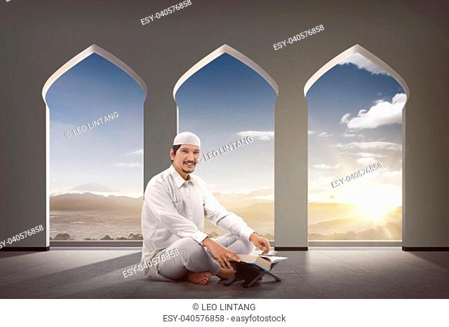 Religious asian muslim man with Koran sitting on the mosque
