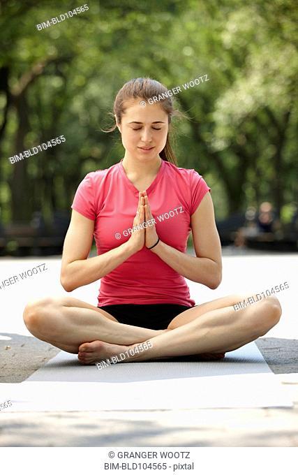 Caucasian woman practicing yoga in park