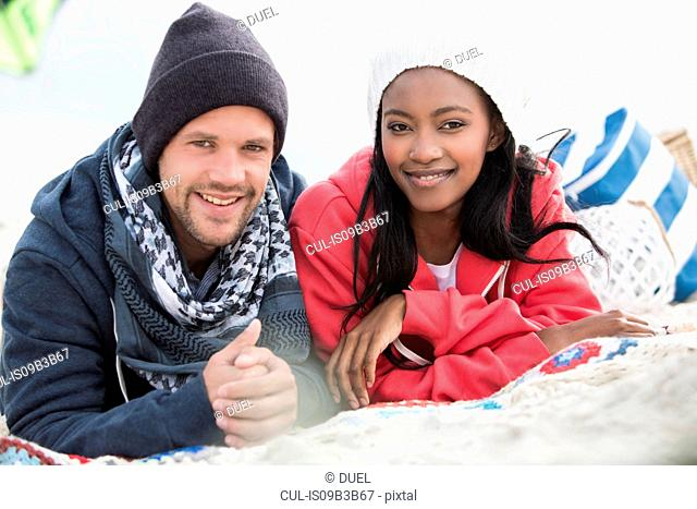 Portrait of young couple lying on picnic blanket at beach, Western Cape, South Africa