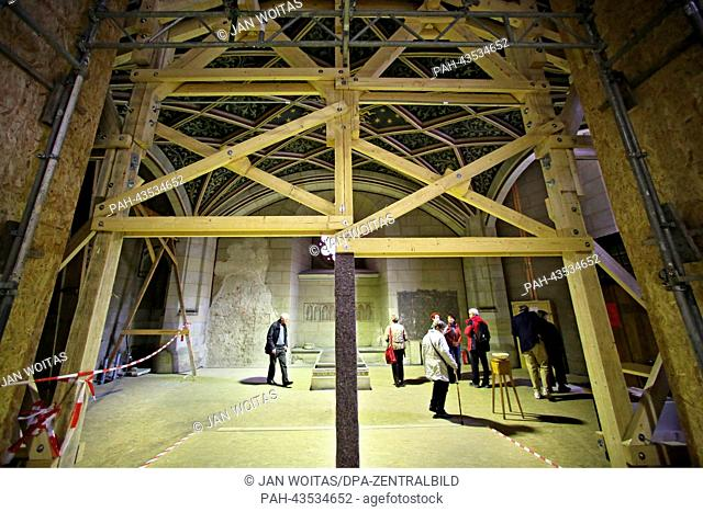 Visitors look at the grave of Martin Luther during a tour of the construction site at All Saints' Church in Wittenberg,Germany, 08October 2013