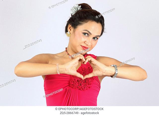 Woman in formal attire making heart with hands