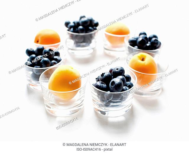 Still life with circle of apricots and blueberries in glass tumblers