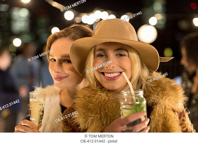 Portrait smiling young women drinking cocktails at party