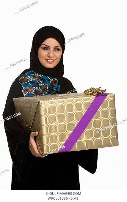Young woman holding gift, smiling, portrait
