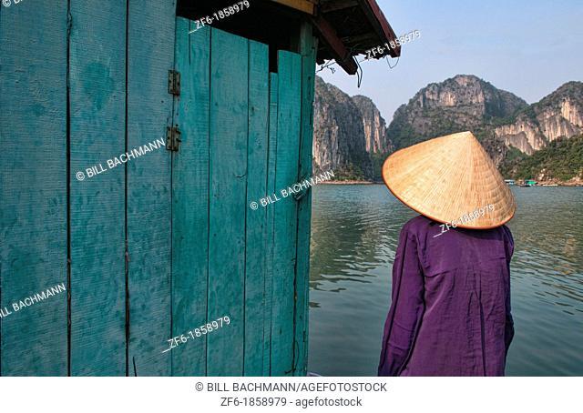 Picturesque scene old woman in purple in fishing village in Halong Bay Ha Long relax Vietnam