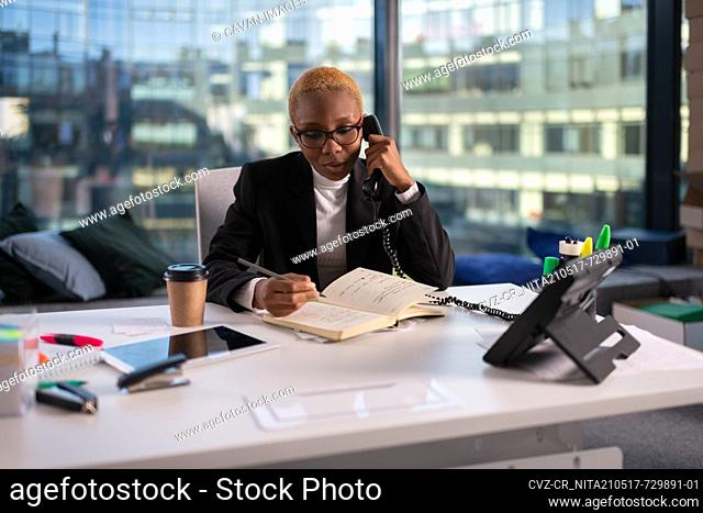 African American businesswoman making notes during phone call