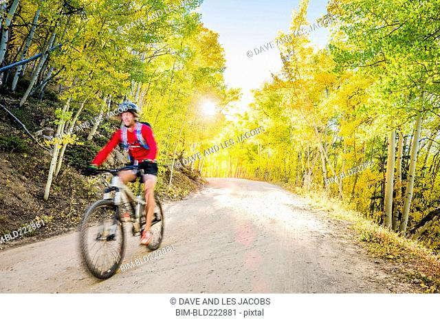Caucasian man riding mountain bike on forest path
