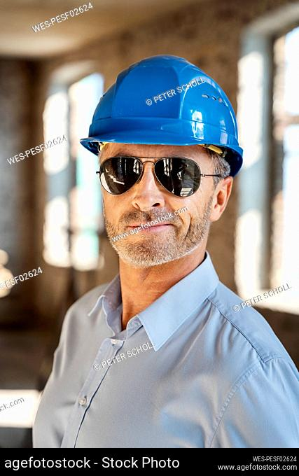 Architect wearing sunglasses and hardhat smiling while standing at construction site