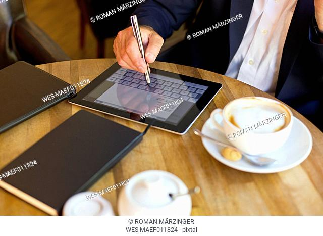 Businessman sitting in a coffee shop using digital tablet, partial view