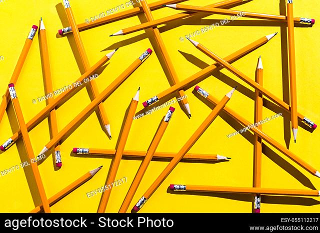 Pencils: pattern of orange pencils from above on yellow background. Office and school concept
