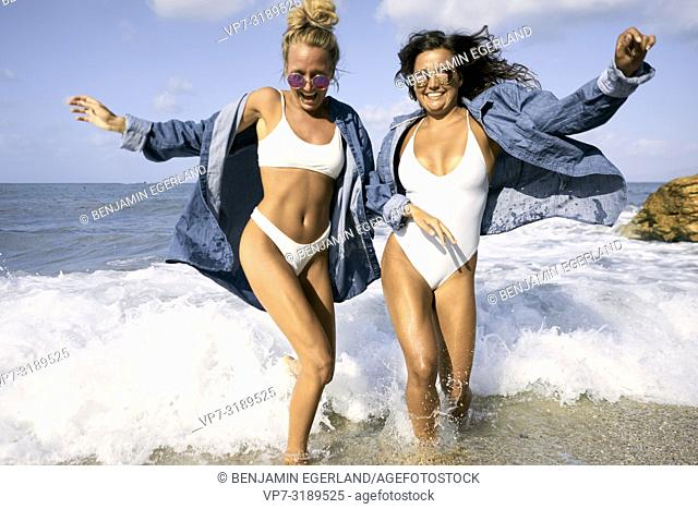 Two women in sea water at beach, Chersonissos, Crete, Greece