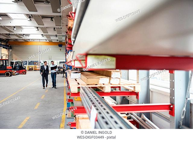 Two men walking and talking in factory shop floor