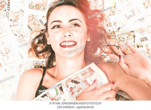 Avant-garde photograph with red tone fade of a vintage pretty pinup woman with red lips and curly hairstyle hugging pages from her prized comic book collection