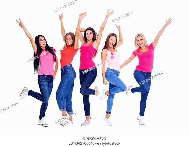 Friendship, party and people concept - group of smiling girlfriend dancing and jumping in studio, blank shirts with pink breast cancer awareness ribbon