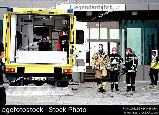 22 August 2020, Berlin: Firefighters pass an intensive care transporter of the German Federal Armed Forces, which stands in front of the Charite