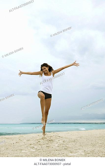 Young woman jumping in air on beach