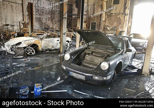 17 March 2020, North Rhine-Westphalia, Neuss: Burnt-out sports cars are standing in a hall. A firefighter was slightly injured in a fire at a warehouse in Neuss...