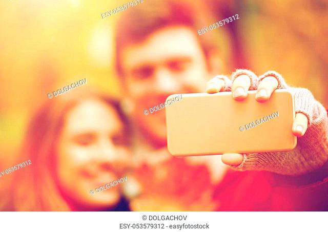 love, technology, relationship, family and people concept - happy couple taking selfie by smartphone in autumn park