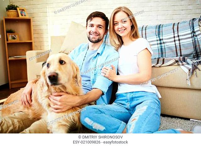 Happy young couple and their pet enjoying home rest on weekend