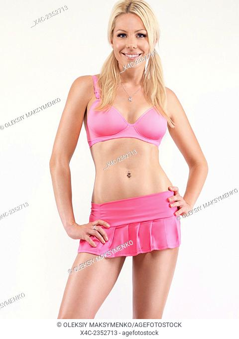 Glamorous young smiling pretty woman with blond hair in sexy pink skirt and sports bra isolated on white background