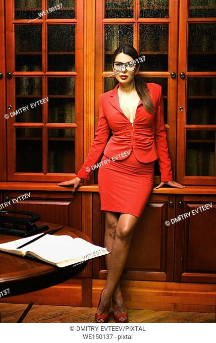 Portrait of librarian in red strict suit in vintage interior