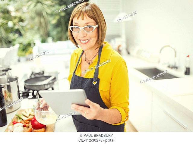 Portrait smiling mature woman with digital tablet cooking in kitchen