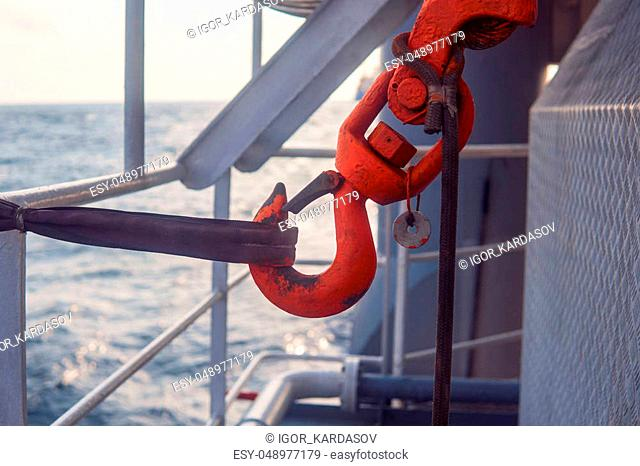 Offshore crane hook is secured for sea passage. Cargo operations at sea