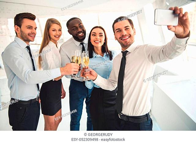 Successful business people are drinking champagne, talking and smiling while celebrating in office. One guy is doing selfie