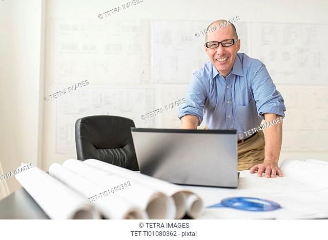Portrait of smiling mature architect using laptop in office