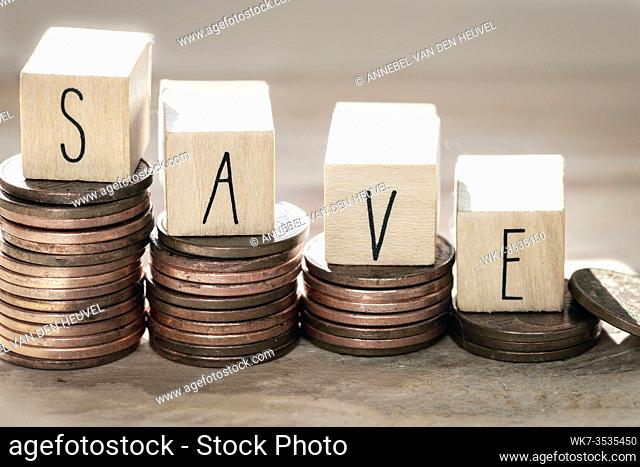 Stack of coins with save letter in wooden block, Time to Saving Concept growing money stairs close-up