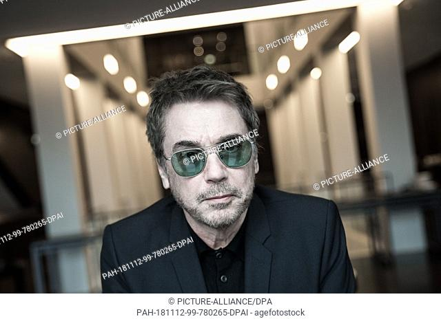 """12 November 2018, Hamburg: The musician Jean-Michel Jarre is standing at a table at a photo shoot in front of a press conference on """"""""Winter Of Moon"""""""" at Arte"""