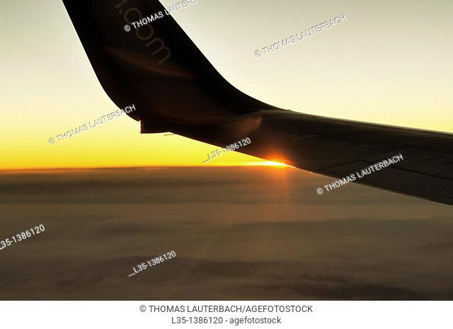 Position light of an aircraft in flight above the clouds at sunset