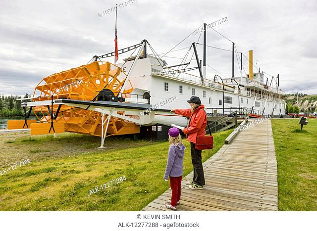 Mother and daughter stand on a boardwalk looking at the SS Klondike, Whitehorse, Yukon Territory, Canada, summer
