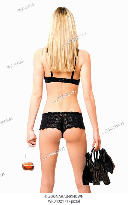Sexy woman with handbag and bottle in her hands. Rear view