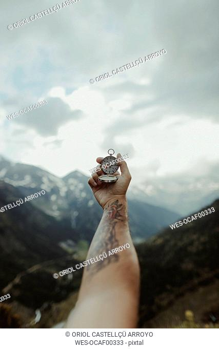 Andorra, tattooed man holding compass, partial view