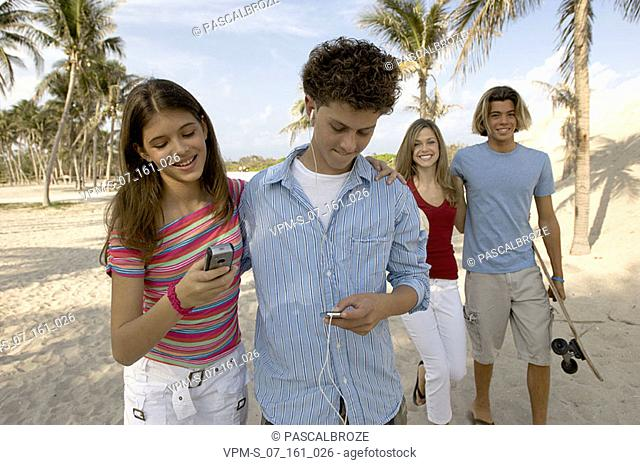 Two young couples walking on the beach and smiling
