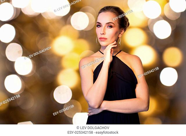 people, luxury, jewelry and holidays concept - beautiful woman in black wearing diamond earring and ring over lights background